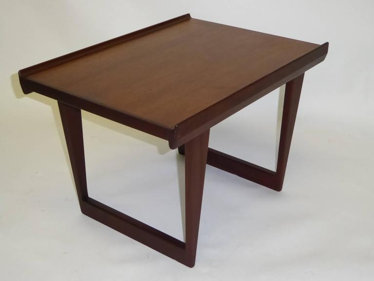 This teak side table or coffee table was designed by Peter Løvig Nielsen and manufactured by Løvig in the 1960s in Denmark. It is made with two tones of teak. Branded on the underside Lovig Dansk Design and stamped twice 1963. This piece is in a