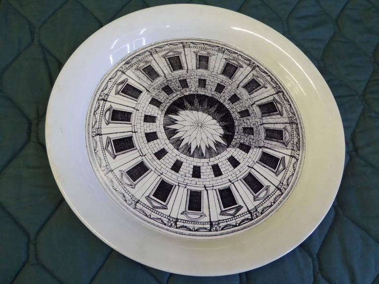 Piero Fornasetti created the Cortile designs in 1954. Showing polygonal courtyards, seen from above, they differed from the dome designs which are seen from below. This metal tray from his studio features a rolled edge in antique cream enamel with