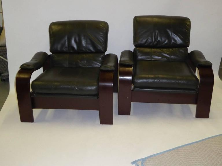 REDUCED FROM $3,450. Pair of green leather and bentwood lounge chairs in the style of Alvar Aalto, the iconic Finnish designer. Supple and soft dark green leather cushions and arm pads highlight this pair with dark brown painted wood forms with the