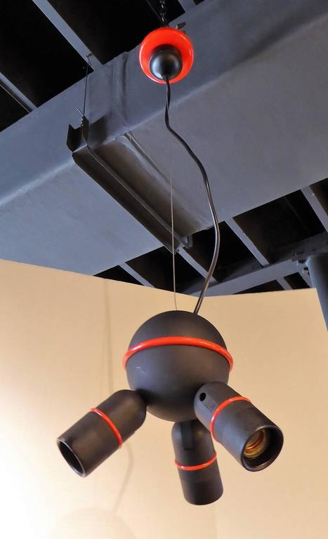 Roger Tallon (1929-2011), world re-known French Industrial designer. A black with red accents three light fixture, edited in France by Lifa. The arms are fully adjustable in direction. Side to side, up, down. Takes three standard Edison base