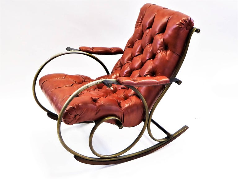 REDUCED FROM $1,500. With a Mid-Century styling inspired by turn of the century Edwardian tastes, this Lee L. Woodard designed rocking chair is most comfortable and the tufted leatherette upholstery divine. With a antiqued brass finish over nickel