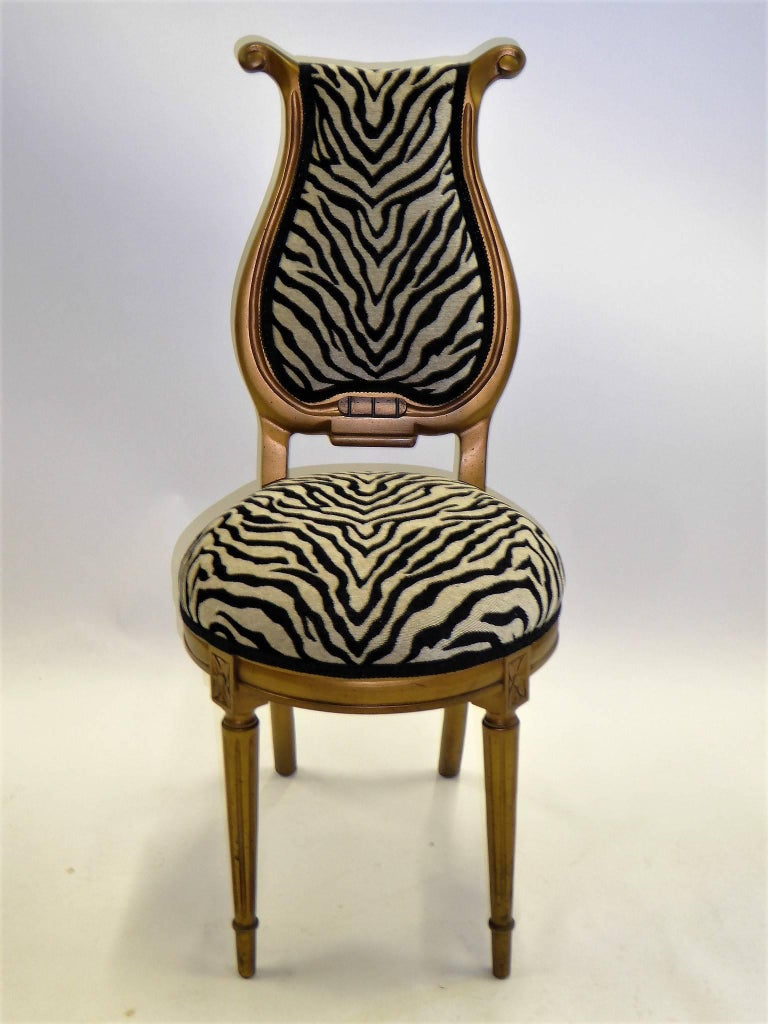 1940s stylized musical motif side chair upholstered in luxe chenille zebra fabric. With a streamline modern lyre shaped back and Louis XVI style front legs, it has soft gilt gold finish.   Measurements: 39 inches high back x 17 inches wide x 23