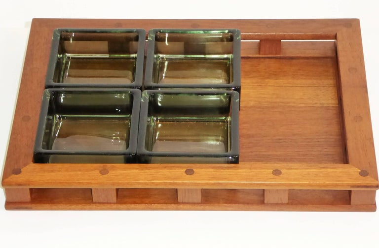 This 1960s Jens Quistgaard designed teak wood serving tray with four thick green glass inserts is from Dansk Designs and made in Denmark. The teak wood of the earlier, Danish-made pieces by Quistgaard was of a higher quality than the later pieces.