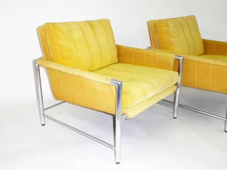 Here a pair of 1960s lounge chairs from Founder's Furniture with polished aluminium frames with a cushioned faux sling style ala Harvey Probber. Requiring new fabric, the original is a bright yellow chenille corduroy with staining. The pair retain