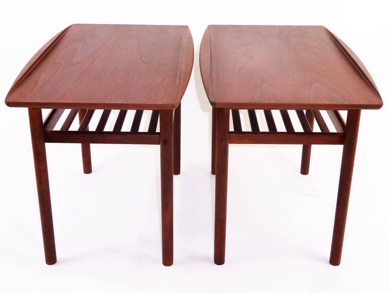 1960s iconic table design by noted Danish designer Grete Jalk and produced by cabinetmaker Poul Jeppesen. Each with a sculpted curled edge and featuring a slatted stretcher shelf. Both have Grete Jalk/Jeppesen labels and Danish Control labels. One