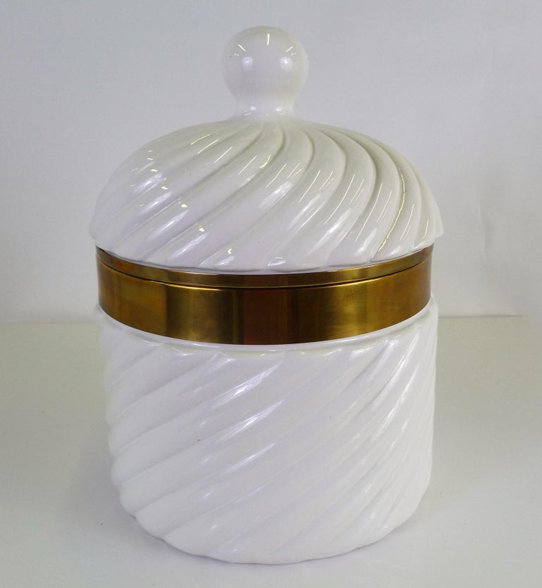 Exhibiting Tommaso Barbi's signature ceramic rope like swirl, this large fat white glazed ceramic and polished brass ice bucket, was created for b ceramiche in Italy. The insert is off- white plastic. Signed on the underside, b ceramiche, for
