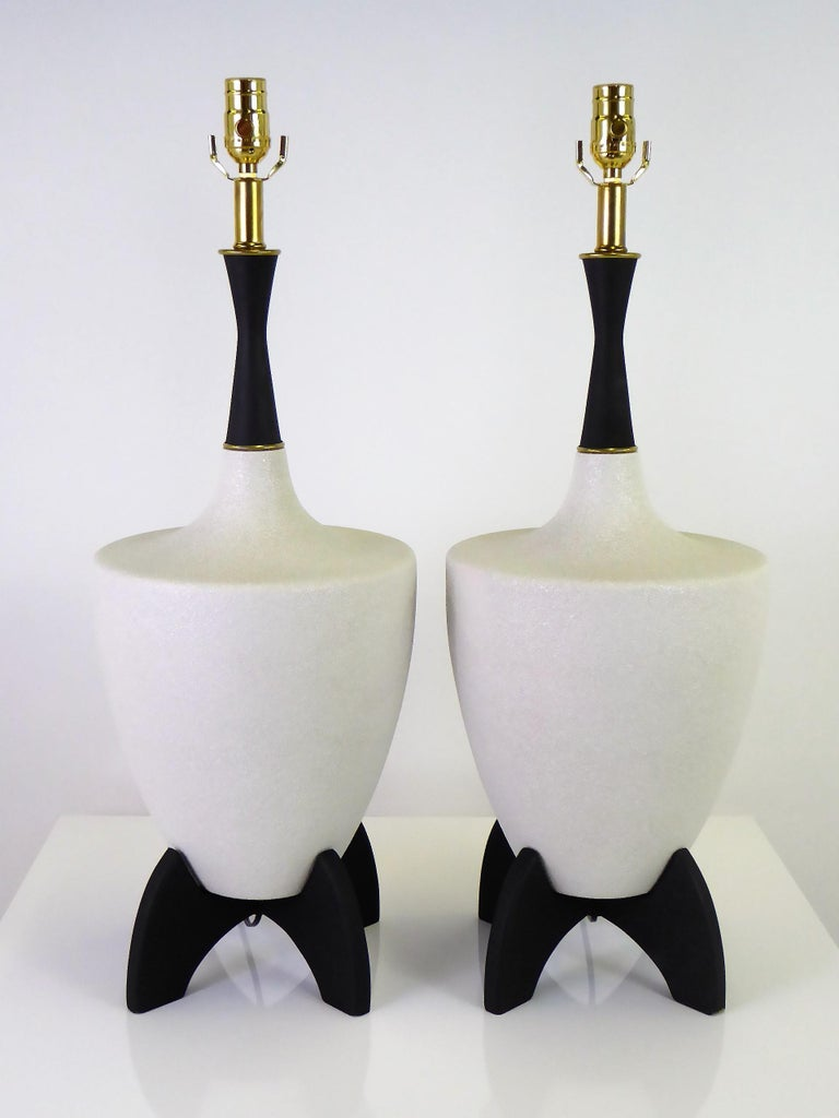 Mid-Century Modern pair of urn shape cream color pebble glaze ceramic with black wooden stand and neck table lamps, 1950s. With brass accents, the lamps have been fully restored, rewired and with new brass UL three level sockets. Takes medium base