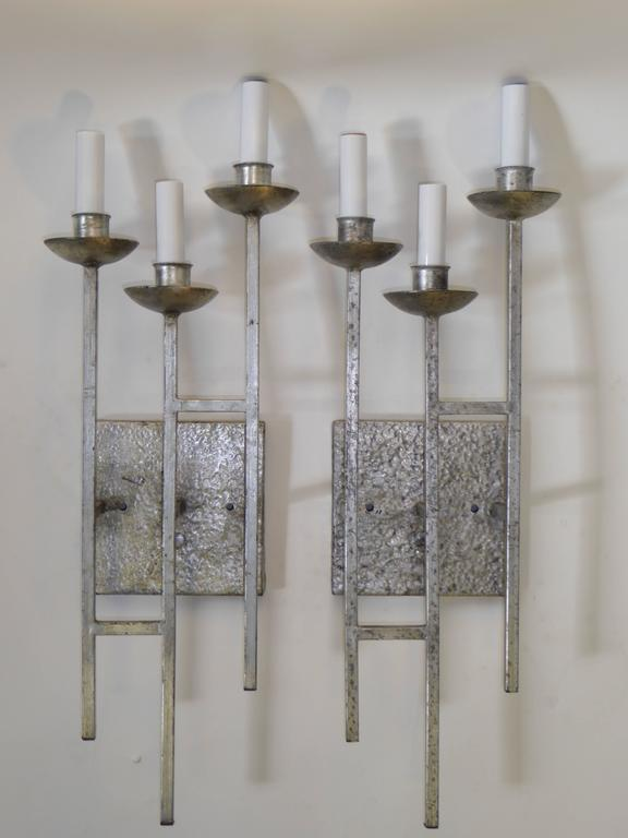 Beautifully realized early 1960's hammered and silvered metal three candelabra light sconces with a staggered grid rectangular form of square rods and cupped bobeches. Early Brutalist design with Paul Evans inspiration. Height measurement is without