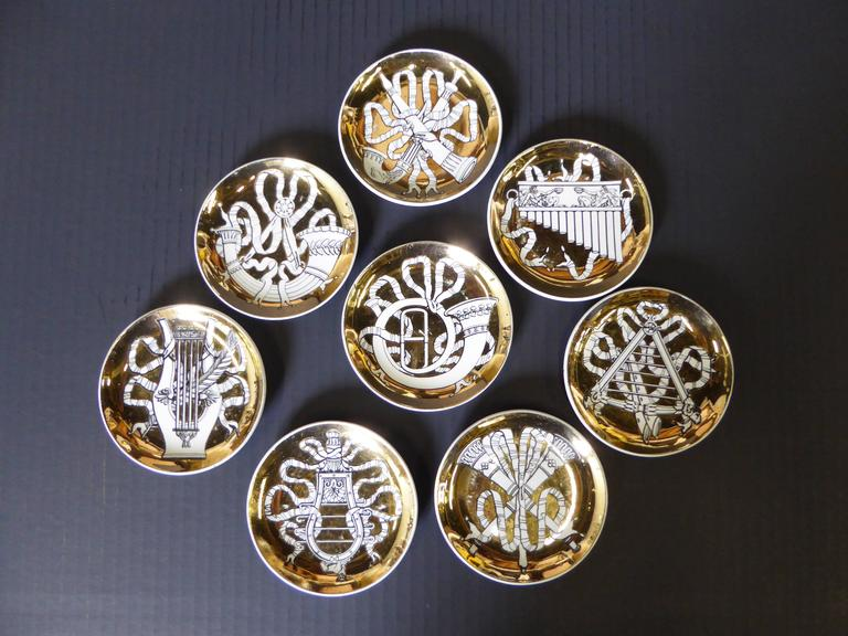 Elegant and pure Fornasetti, these eight gilt, black and white dishes featuring neoclassical visions of musical instruments were an exclusive by Fornasetti for Bonwit Teller. To be used as canapé servers or coasters or perhaps even ashtrays in the