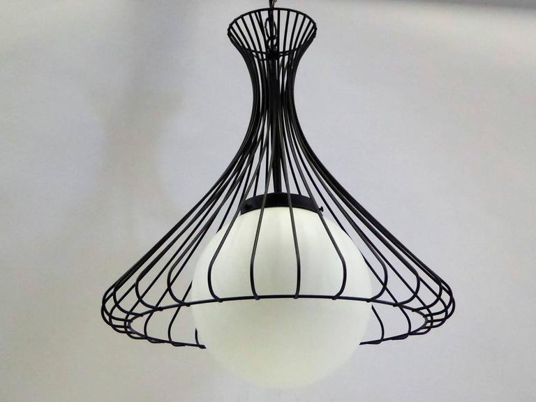 With a 1950s flair, this pendant chandelier has a steel wire bell shaped cage over a white satin glass globe. Rewired, restored and with new UL brass inner socket. Takes single medium base bulb, 75 watts max. The fixture is 20 inches in diameter and