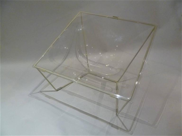 This Contour lounge chair was designed in the 1960s by David Colwell and manufactured by 4's Company Ltd. in the United Kingdom. The process required to hand stretch a hot flat perspex or acrylic sheet to be clipped onto a steel rod frame. Colwell's