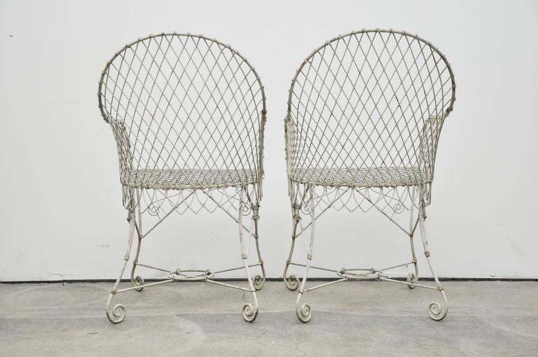 A pair of vintage 1920s French wire garden chairs. Wire painted white.