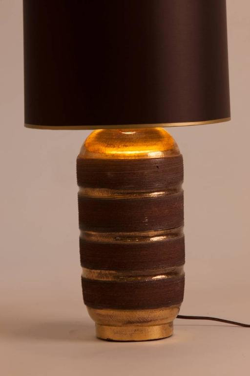 French Mid-Century ceramic lamp featuring gilt glaze accented by textured bands of dark chocolate. Coordinating dark brown silk shade with gold gilt interior and coordinating gold ribbon detail. Lamp has been rewired for the US.