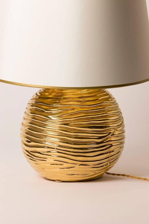 Mid-Century Modern French table lamp. Lamp is ceramic and features bright gold glaze which accents the ripple motif. Custom silk shade with gilt lining created in Paris.