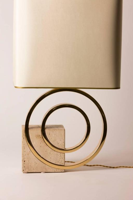 Mid-Century French table lamp featuring a brass circular body anchored by a geometric stone square. Custom gold lined silk shade created in Paris. Lamp has been rewired for the United States.