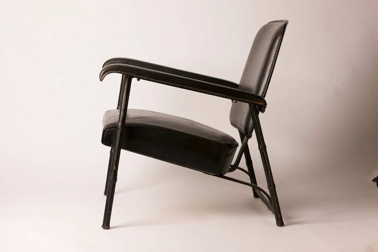 Rare and handsome hand-stitched French leather lounge chair by famed designer Jacques Adnet. Chair features a metal body covered in luxurious hand-stitched leather. Chair is in excellent vintage condition.