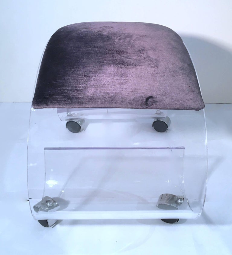 Stylish and charming Lucite scrolled rolling bench or vanity stool upholstered in a purple/gray velvet. Please contact for location.