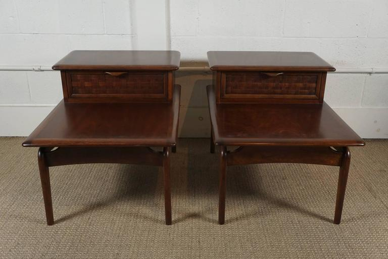 Here is a beautiful pair of walnut stepped tables with a basket weave drawer front. The tables have accent brass spheres that add a nice detail. Newly refurbished, the tables have a a beautiful satin finish and are in excellent condition. The height