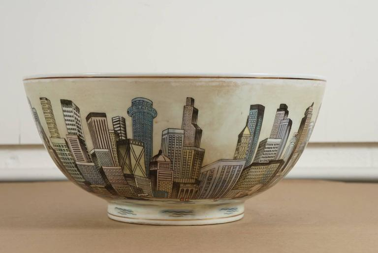 Here is an amazing large porcelain bowl with a full surround cityscape a view of the harbor. The city appears to be fictional with various styles of skyscrapers. There are no marks or signature on this unique work of art.