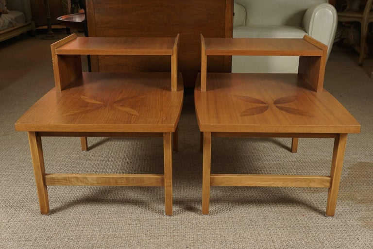 Here is a great pair of Mid-Century Modern stepped end tables in a light maple finish. The honey toned color is complimented by a striated leaf pattern centre inlay. The tables have a very sharp and polished look. Measure: The bottom shelf is 14.75