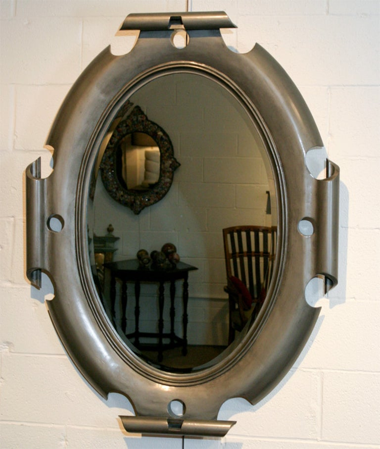 This unique oval shield mirror with a scroll motif makes an elegant yet bold statement. It is made of wood but has the appearance of iron with a rubbed graphite finish. Custom orders available.