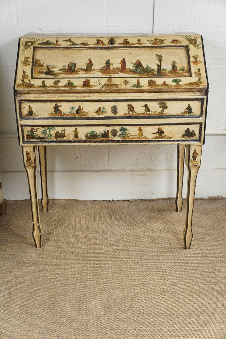 Here is a charming painted Italian desk with decoupaged figures and scenes. The desk has a drop front with link chain that has been recently added but not shown.