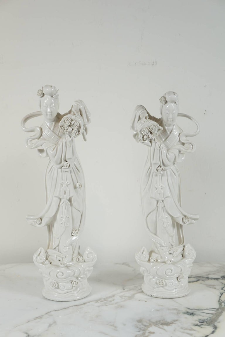 Here is a lovely pair of Blanc de Chine figurines with flowing lines and intricately carved flower details.