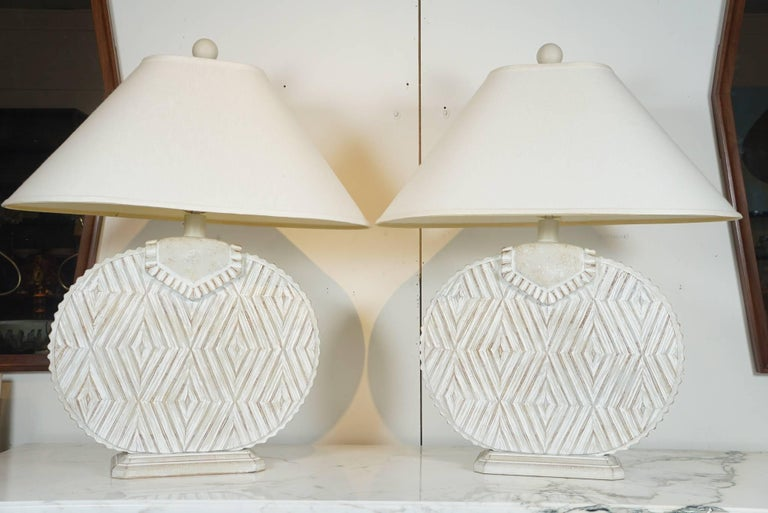 Here is a great pair of ceramic lams with a raised and textured aztec pattern. The lamps have a two tone finish with a pale white washed contrast. As shown with the shades, the lamps are 27 inches high. Newly wired and with new brass hardware.