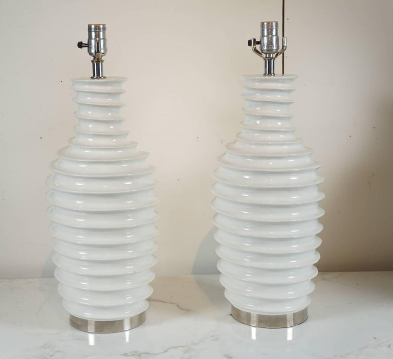Here is a great pair of modern lamps in white porcelain and a spiral motif. The lamps have chrome hardware and a fitted chrome base. While in over all great condition there are a few minor bites on some of the spiral tips that are not very
