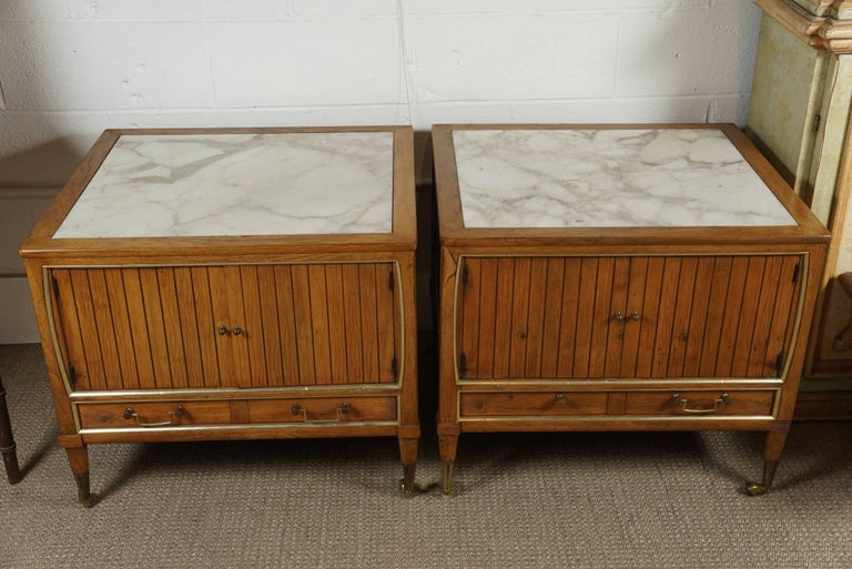 Here are two modern end tables with a maple finish and inset marble tops. The tables have brass hardware and casters.