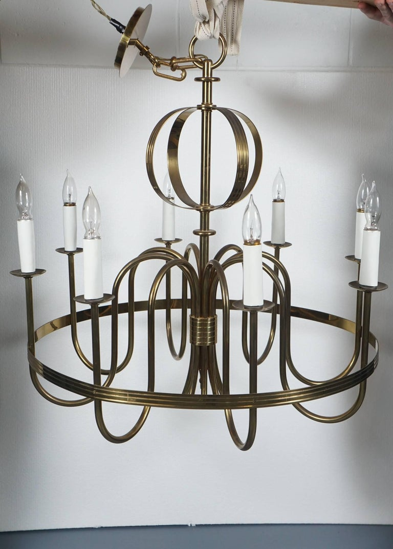 Here is a beautiful Tommi Parzinger chandelier in brass. The chandelier features eight curvilinear arms and is enhanced by a modern top sphere. The candle sleeved sockets take regular sized bulbs and can have attached shades. This piece is newly