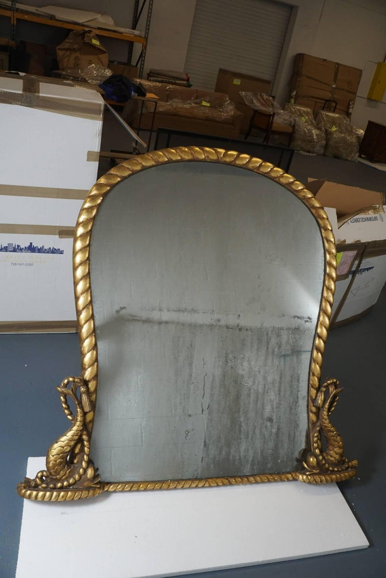 Here is an amazing and beautiful Regency gilded mirror with a hand carved roped motif and double sided dolphin base. The mirror insert has a natural antique finish and is backed with wooden slats. The large scale makes this mirror suitable for a