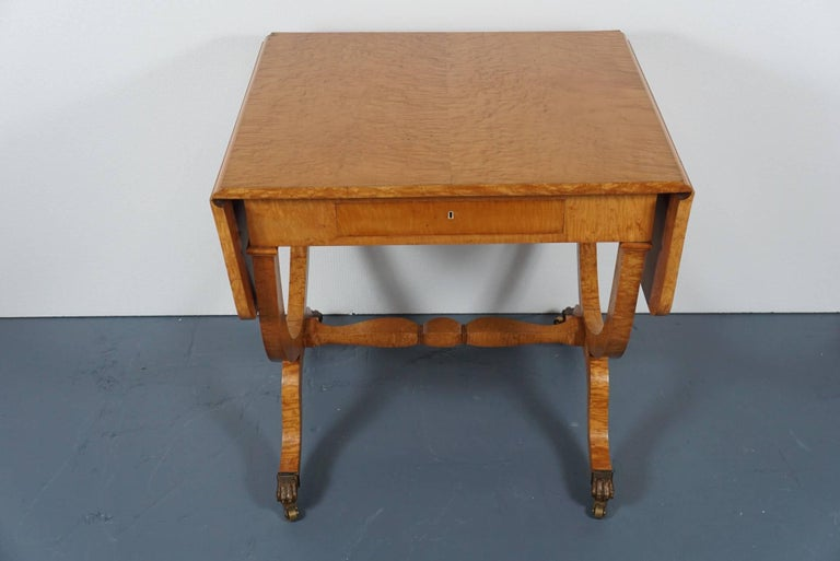 Here is a gorgeous Biedermeier drop leaf table in maple. The table has two 10 inch leaves and features an elegant stretcher base with brass capped claw feet and casters.