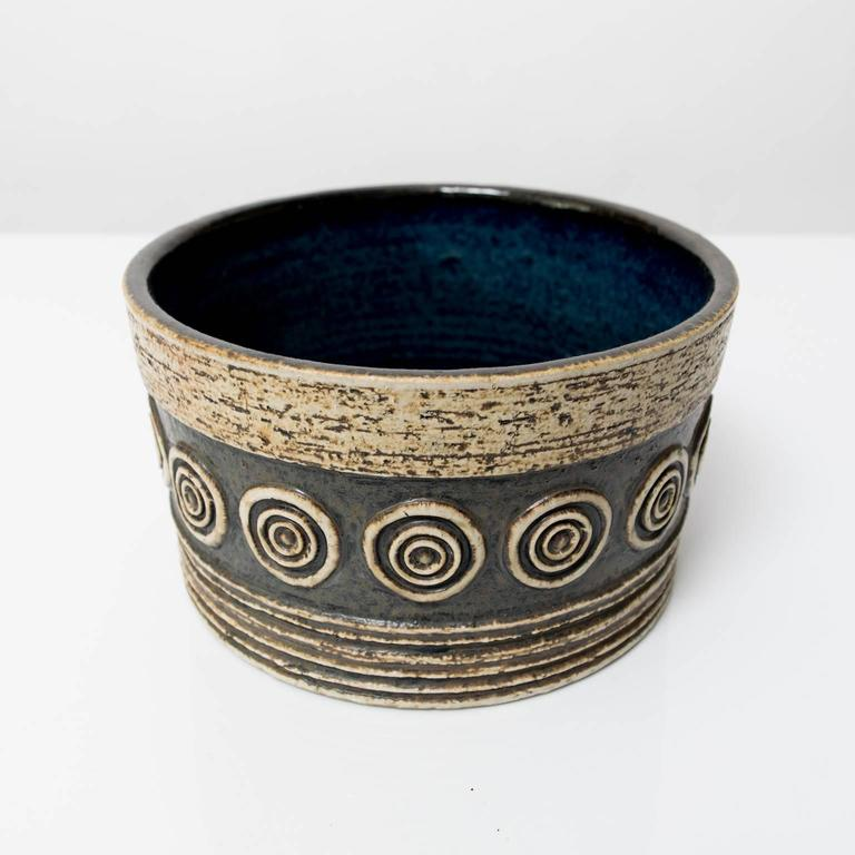 A Scandinavian Modern studio bowl by Britt-Louise Sundell for Gustavsberg, circa 1960. This piece is highly textured with horizontal grooves, circles and glazed in earthy, neutral colors and a deep blue inside.