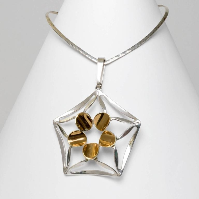A silver necklace with pentagonal pendant with gilded details. Designed by K.E. Palmberg for Alton, Falkoping, Sweden. Diameter: 5