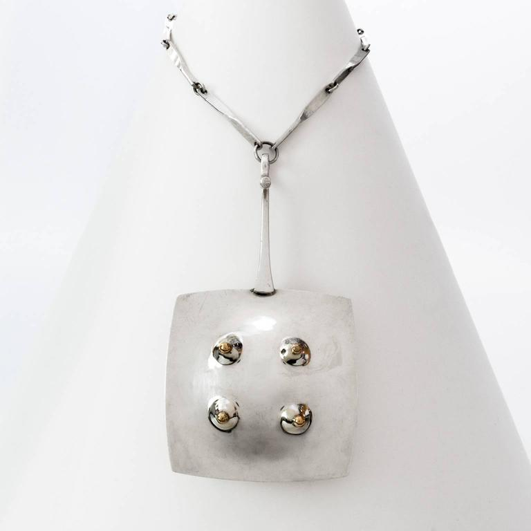 Scandinavian modern sterling silver pendant with gold details, inspired by the early 20th century Surrealism art movement. Made by One Bohlin, Stockholm, Sweden, 1972, with details in gold, original chain. Designed by Ove Bohlin.  Pendant length: