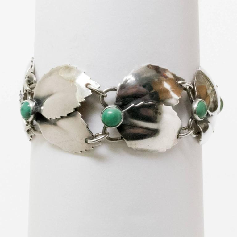"""A Scandinavian Modern silver bracelet with linked overlapping leaves detailed with malachite cabochons. Designed by Gertrud Engel for A. Michelsen, 1950s, Stockholm, Sweden. Diameter: 2.5"""". Height: 1""""."""