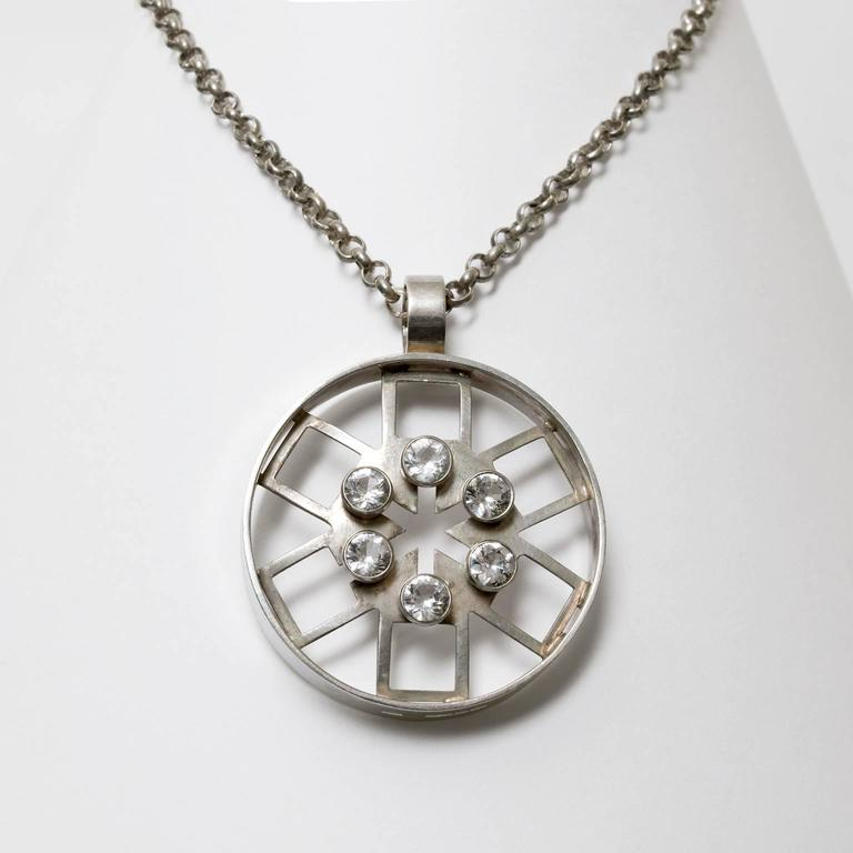 """A silver Scandinavian Modern pendant and chain with a geometric hexagonal design within a circle and detailed with six rock crystals. Made by Kultateollisuus KY Turku, Finland, 1972. Diameter: 2"""". Chain length: 28""""."""