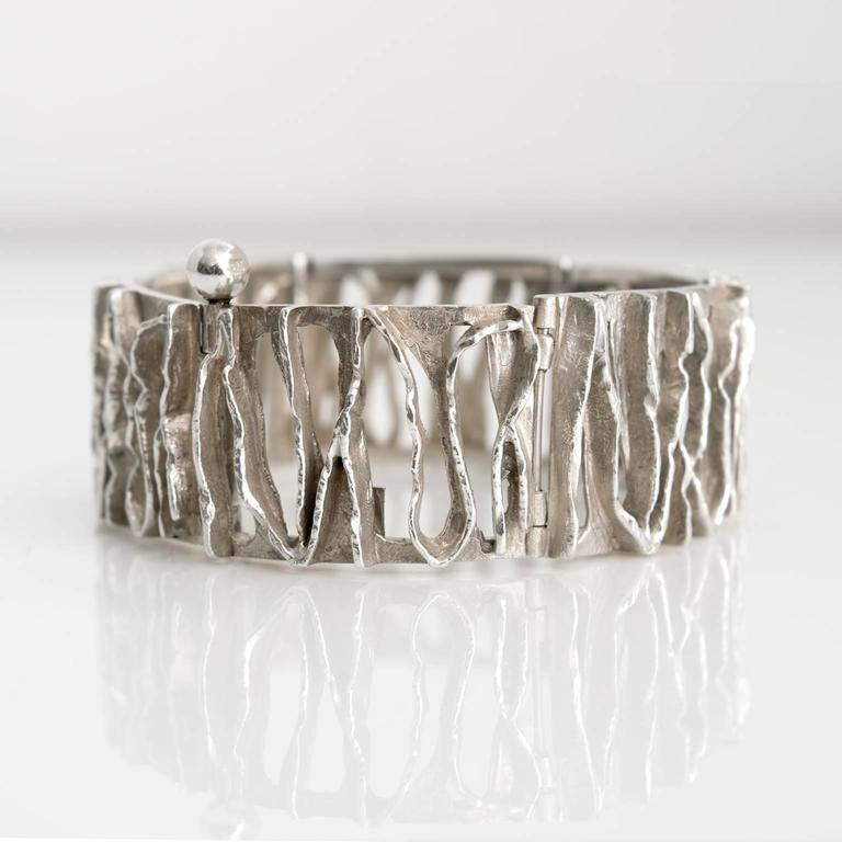 """A Scandinavian Modern Silver bracelet with polished and etched openings from Denmark by C. Holm. Measures: Diameter: 2.5"""". Height: 1""""."""