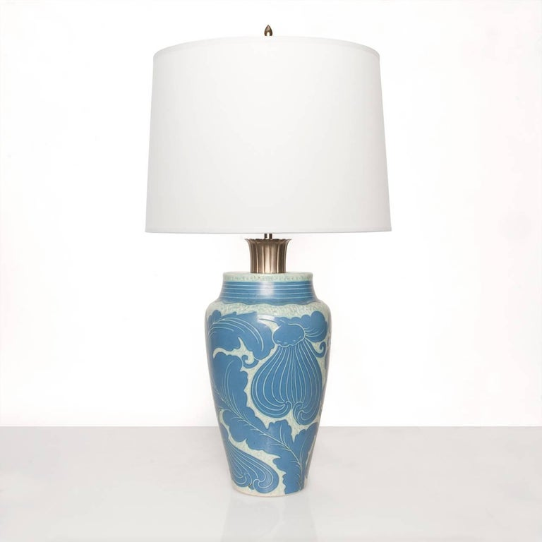 "Swedish art deco table lamp in ceramic ""Sgraffito"" technique with a leaf motif. The lamp has a fluted nickel plated element at the top closure, is newly rewired with a double standard socket cluster for use in the USA. Height 27"","
