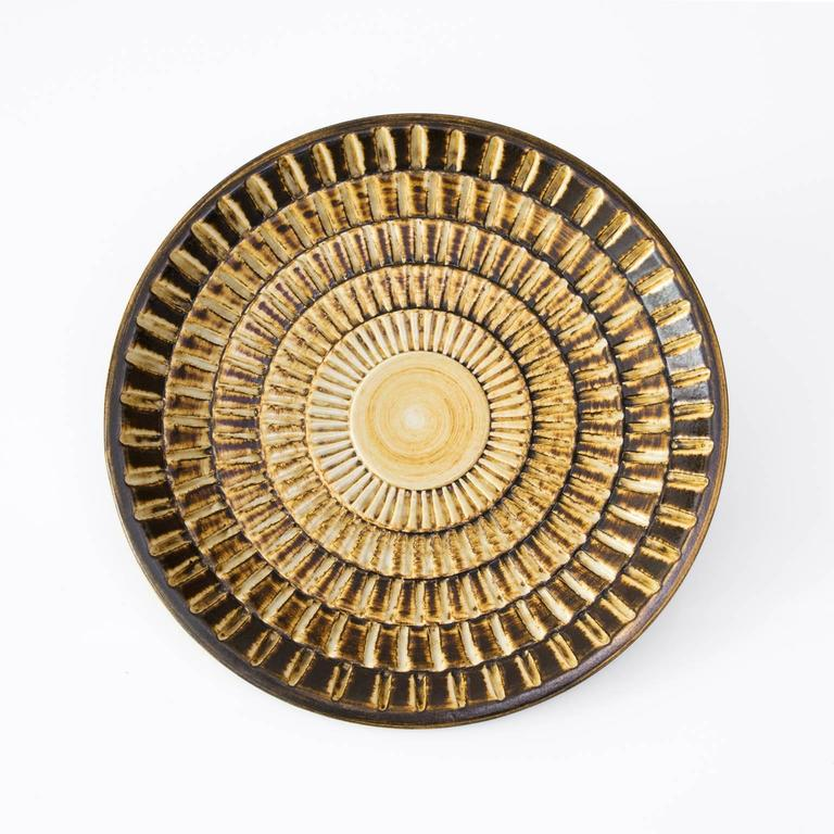 Scandinavian modern ceramic shallow bowl by Gertrud Lonegren in golden glaze and a highly textured surface. Diameter: 11.25