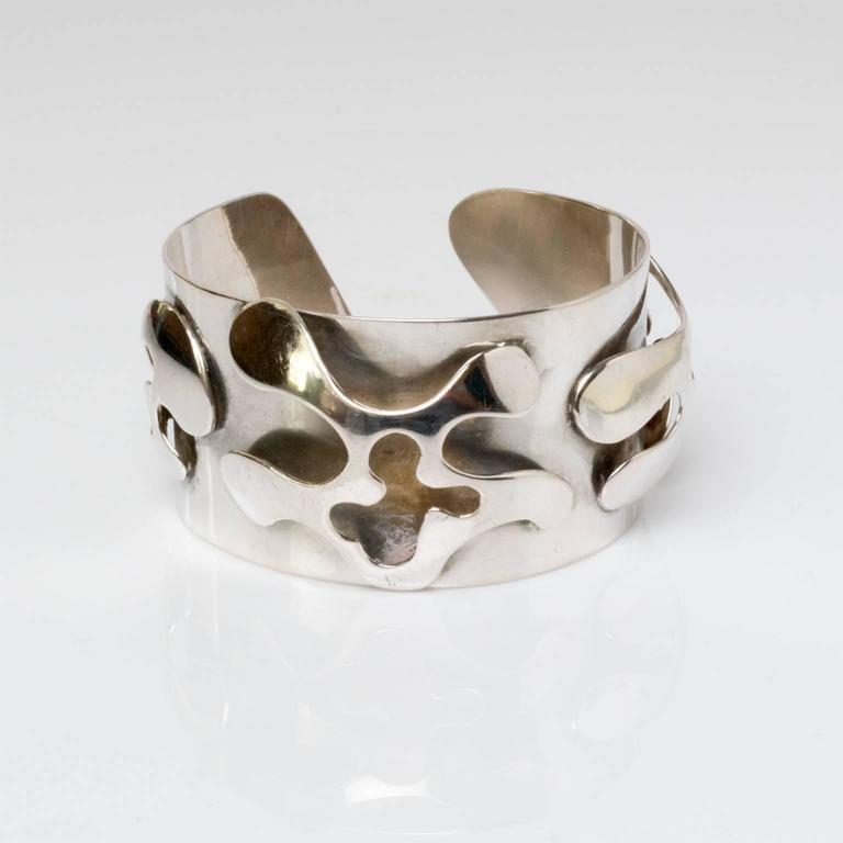 "A Scandinavian modern silver bracelet with a raised cutout surface with free-form organic shapes. Designed Henry Marius Jacobsen, Copenhagen, 1960, Denmark. Measures: Diameter: 2.5"". Height: 1.5""."