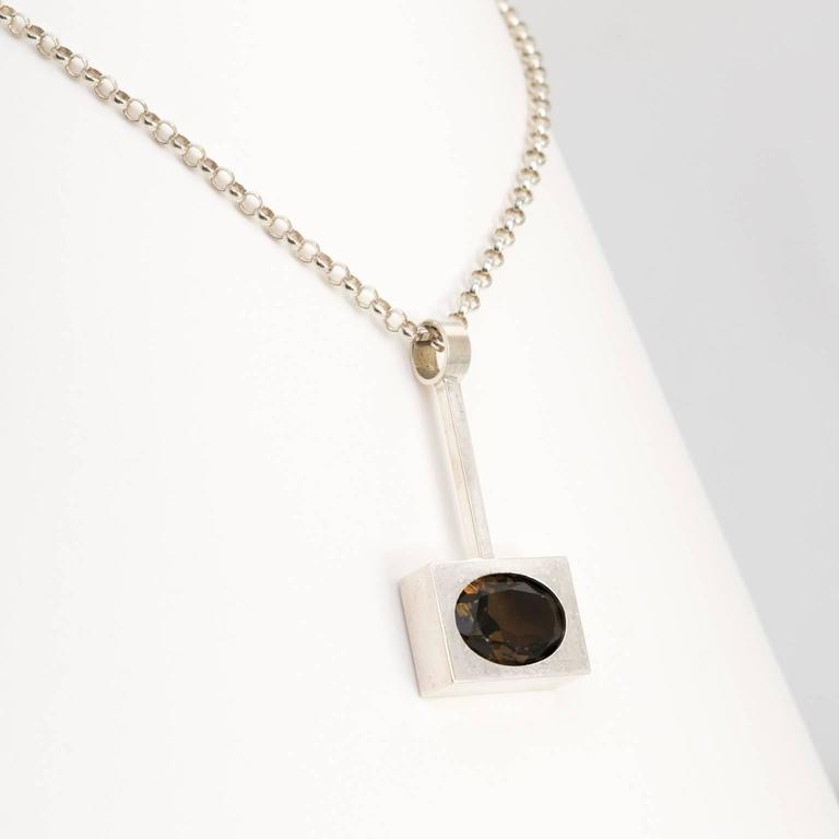 """Silver Scandinavian modern pendant with an inserted oval faceted smoky quartz stone. The chain is also silver. Designed by Kupitaan Kulta, Finland.    Measures: Chain length: 16"""". Pendant height: 2""""."""