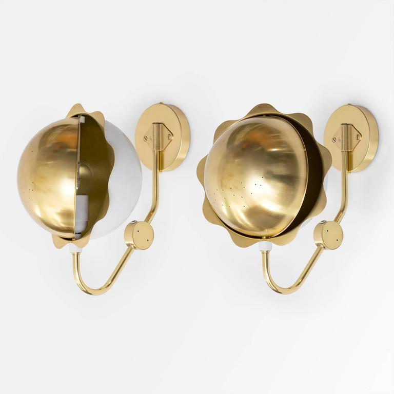 A fabulous pair of Eclipse sconces with adjustable shade and rotatable sphere. Newly polished and lacquered the pair have been wired for use in the USA and are mountable to a standard J-box. The sconces are made in Sweden, circa 1950s. Measures:
