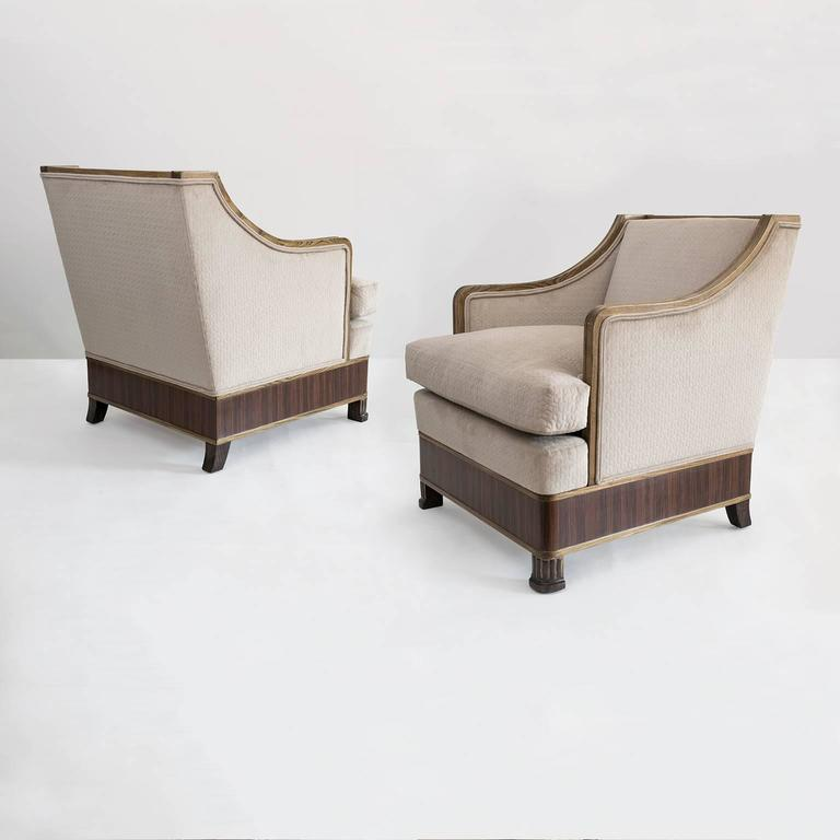 A roomy, stylish and very comfortable pair of Swedish Art Deco upholstered armchairs. Frames are carved solid elmwood with front legs in the form of a columns and a band of rosewood veneer wraps around each chair's base. Newly restored and newly
