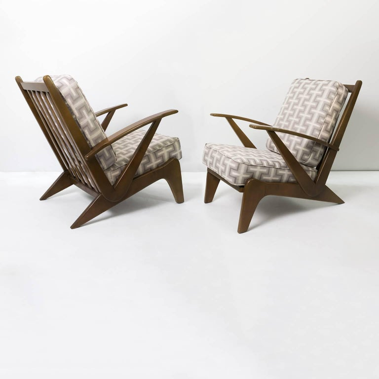 Scandinavian Modern pair of sleek wedge shaped armchairs with newly restored carved wood frames and newly upholstered cushions.
