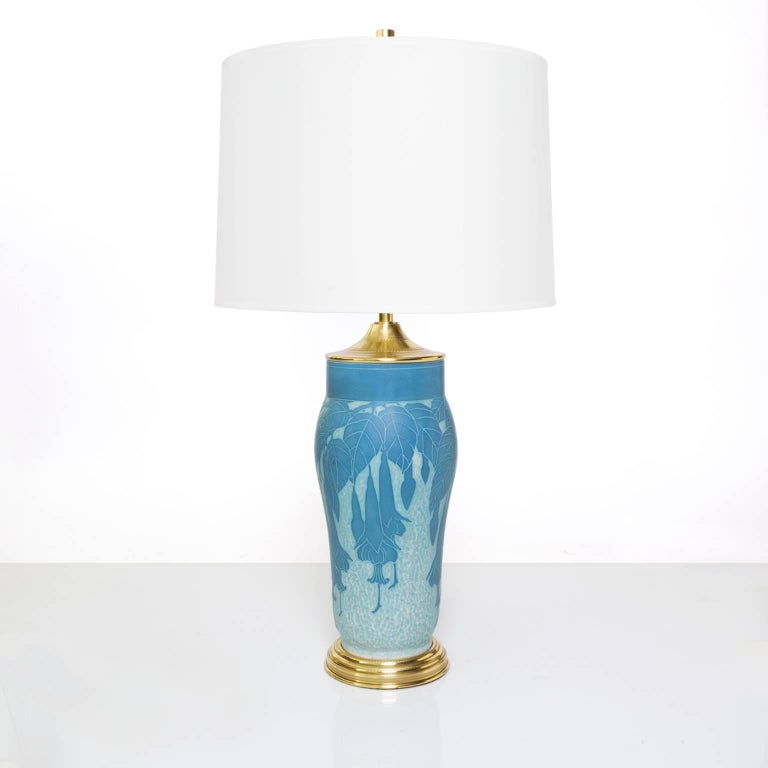 """A Scandinavian Modern, Swedish Art Deco table lamp in ceramic """"Sgraffito"""" technique with a floral vine motif. The lamp retains its original polished brass foot and cap which has been polished and lacquered. Newly rewired with a polished"""