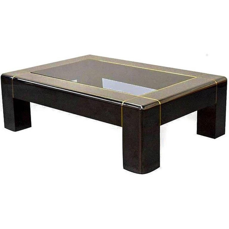 Exceptional, iconic Parsons style coffee table in heavy gunmetal with a smoked glass inset top and brass pinstripe inlay. Pictured in the Karl Springer catalog. In overall great condition, with a few minor wear areas.