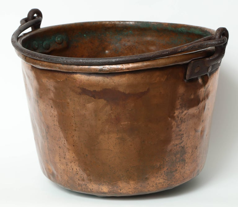Impressive 19th century large copper vessel with a hand-forged iron handle. Cauldron has a great warm patina and would be great as a large cache pot or firewood holder.