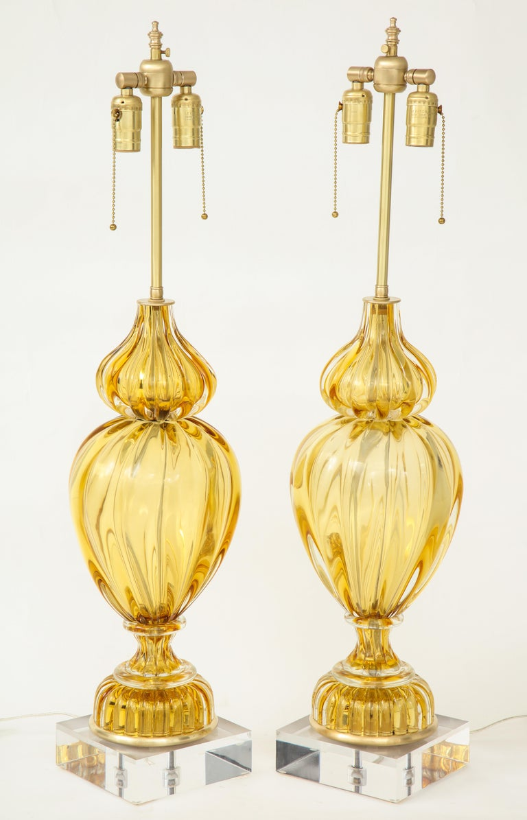 Striking pair of fluted Murano glass lamps in a light amber color with brass fittings sitting on custom Lucite bases. Rewired for use in the USA with brass double pull chain sockets. Seguso glass for Marbro.